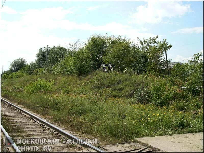 """За переездом мы вступаем во владения станции  """"Яничкино """", ныне исключительно грузовой.  Высокая насыпь с тупиком..."""